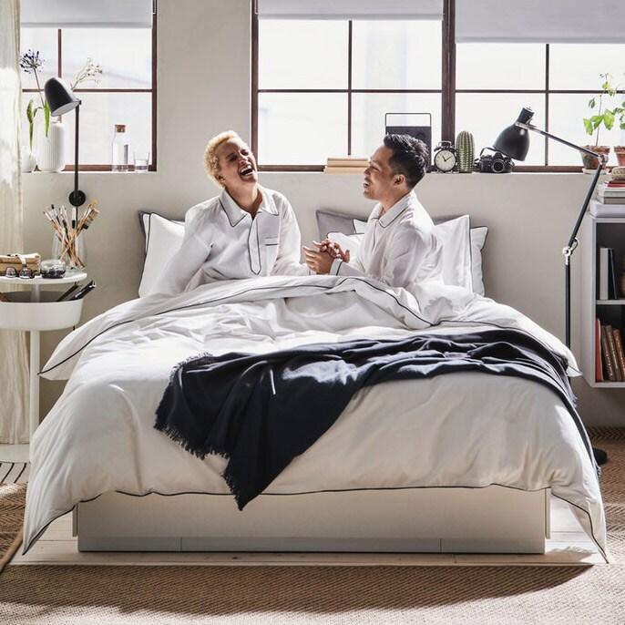 Et par sidder i en seng med hvidt sengetøj og griner.
