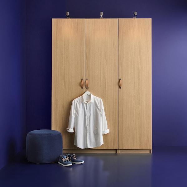 Et PAX garderobeskab i et blåt rum med en knage på dørhåndtaget, hvor der hænger en hvid skjorte, samt et par sko på gulvet.