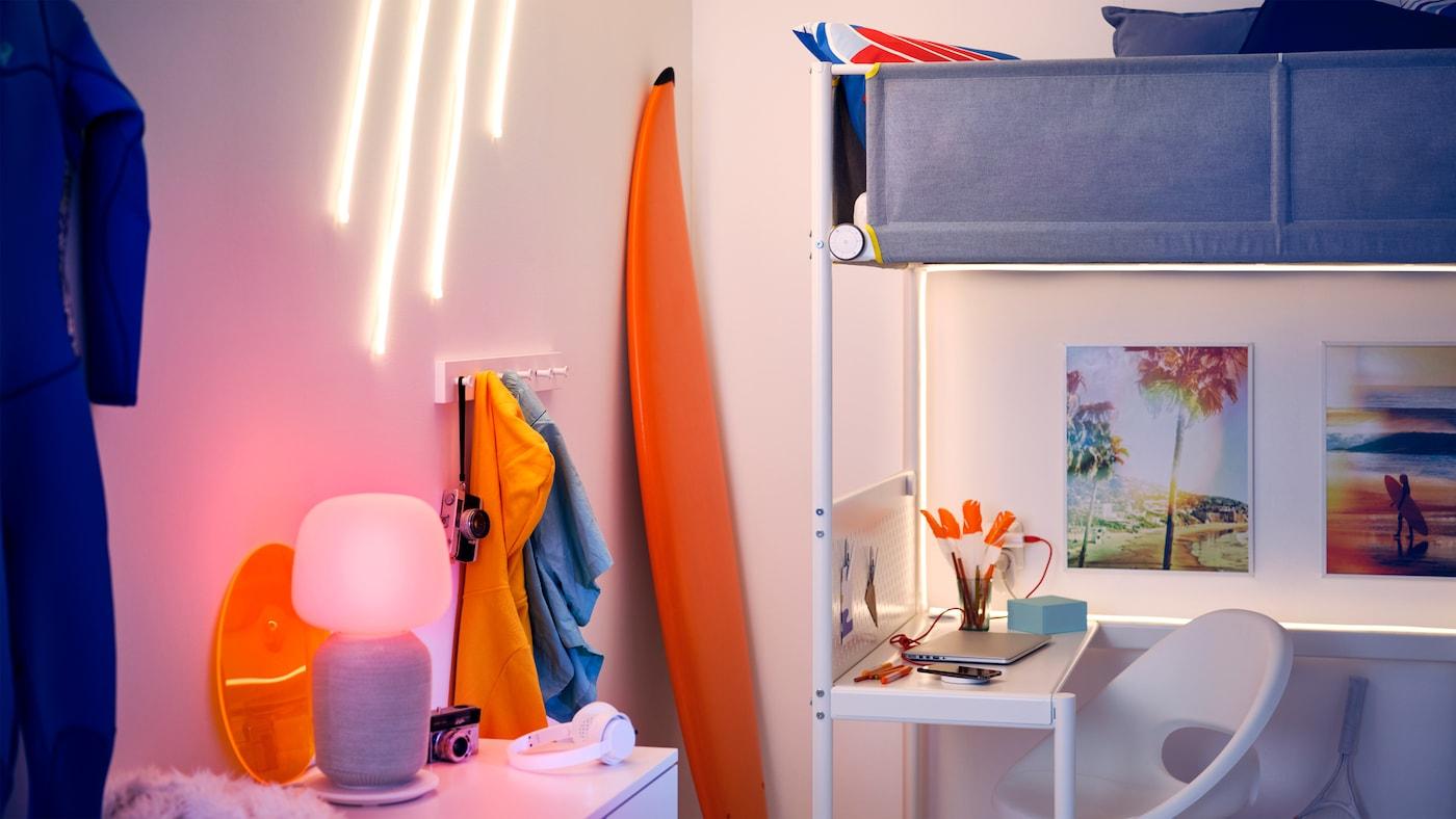 Et rom med en ung, sporty stil, lyslister, en trådløs bordlampehøyttaler, et trådløst kontrollsett og en trådløs mobillader.