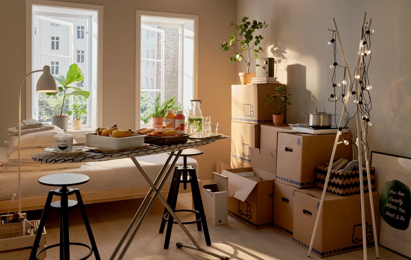 Et rum med flytterod: Stablede flyttekasser, en lille buffet serveret på et strygebræt og en EKRAR stumtjener pyntet med lyskæder.