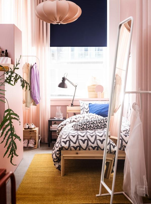 Et smalt rum i lyserøde nuancer med en GRIMSBU seng, et højt KNAPPER spejl og masser af plads til at opbevare og udstille tøj.