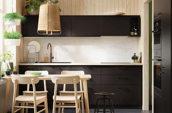 Et sort køkken med lys træbordplade, i lyse omgivelser.