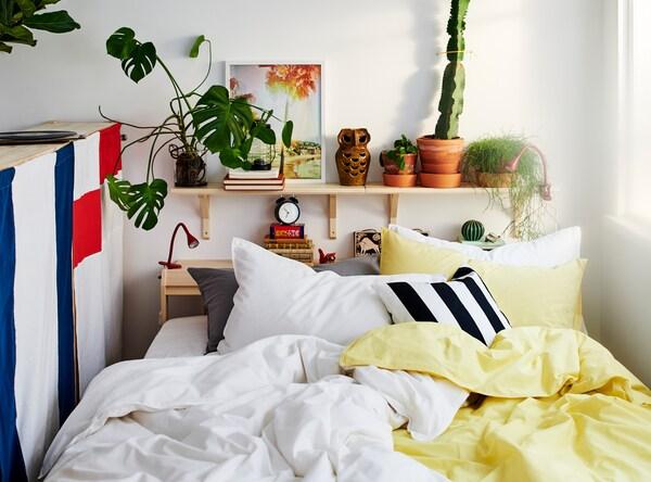 Et «soverom» mellom et vindu og en oppbevaringsenhet, med masse puter og gult, hvitt, svart og grått sengetøy.