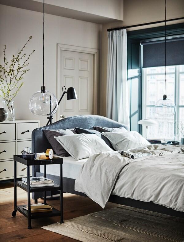 Et soveværelse i i beige nuancer og med en stor grå seng i midten af rummet.