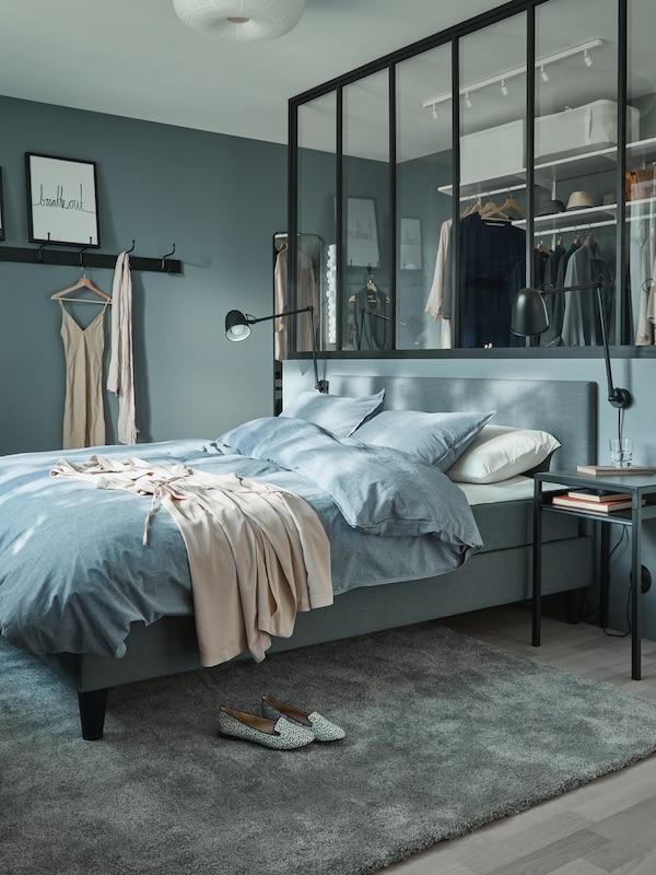 Et soveværelse i med en grå seng, en åben garderobeløsning bag ruder i new-yorker-stil