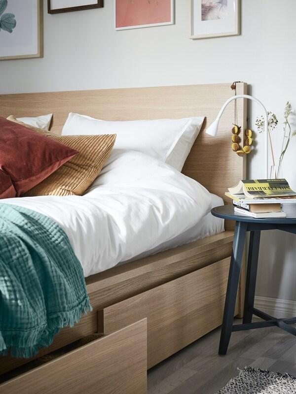 Et soveværelse i med en træfarvet seng og puder i støvede farver. Der står et sengebord ved siden af.