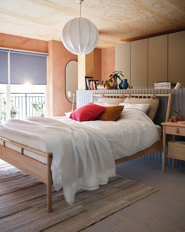 Et soveværelse med en seng i bambus. Væggene er orange.