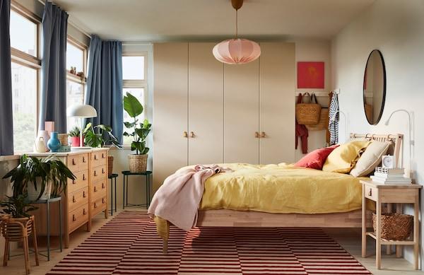 Et soveværelse med seng, kommode og sengebord i naturmaterialer. Et skab i beige og et rundt spejl. Lampen fra loftet er i lyserød stof.