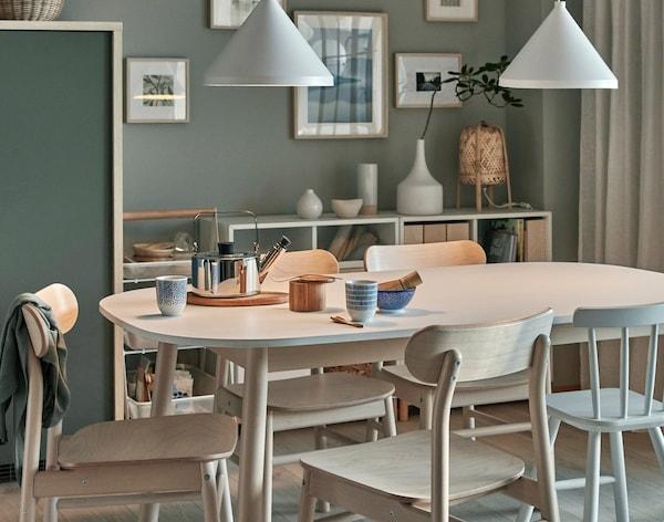 Et spisebord af træ med matchende stole omkring står i en spisestue.