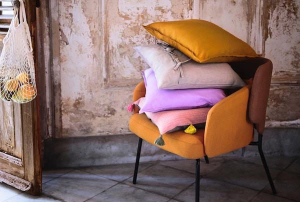 Et stærk organge sofa står i et hvid og grønt rum med farverige puder