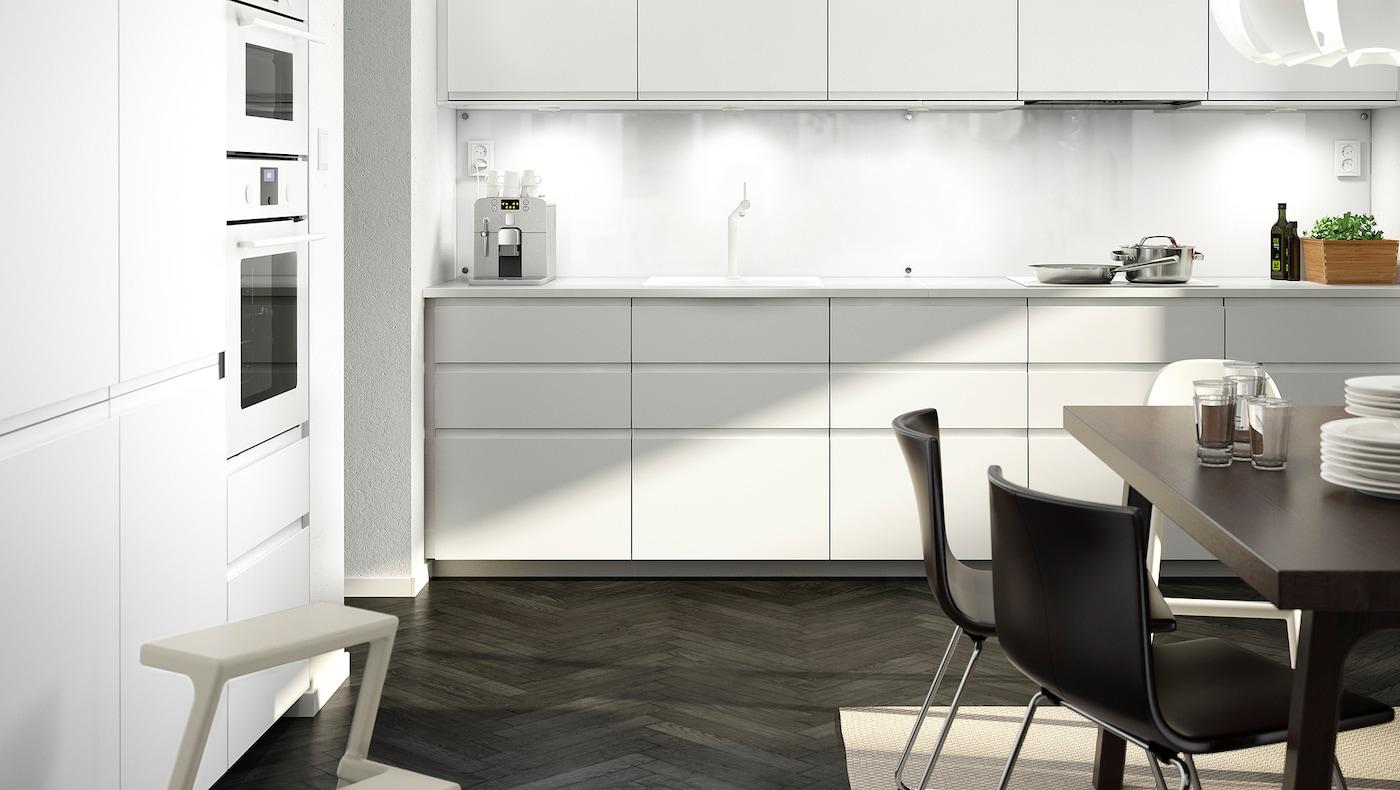 Et stort hvidt køkken med matte hvide køkkenlåger og skuffefronter. Bordpladen er også hvid. I rummet ses et mørkebrunt spisebord med sorte stole.