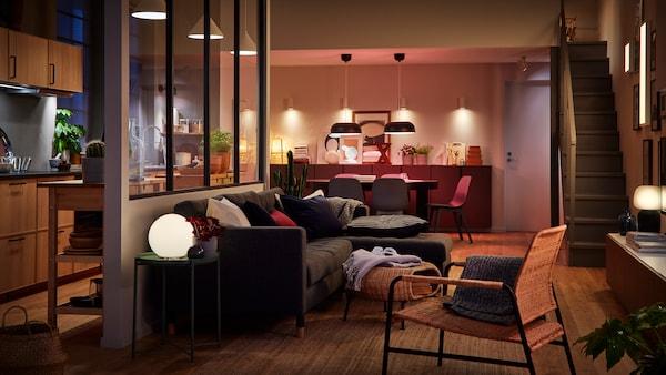 Et stort rom med kjøkken, spiseplass og stue som glir over i hverandre. Et rom opplyst av flere lyskilder.