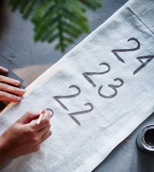 Et stykke stoff blir lagt på tall.