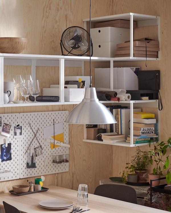 Étagères PLATSA en blanc fixées au mur dans un angle. Elles accueillent des livres, des verres, un mini-ventilateur, etc.
