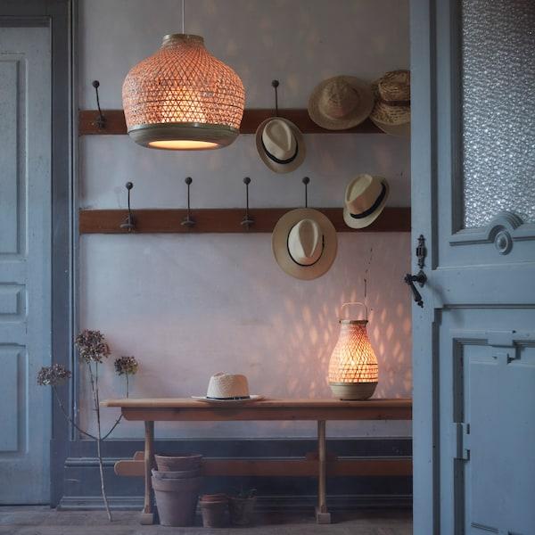 Eteisen katosta roikkuu bambusta punottu MISTERHULT-valaisin. Seinällä on koukkunaulakoita, joista roikkuu panamahattuja. Kapealla pöydällä seinän vieressä on MISTERHULT-pöytävalaisin ja hattu, pöydän alla ruukkuja.