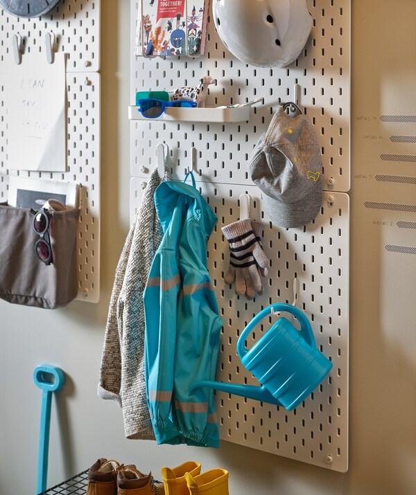 Eteisen seinälle on kiinnitetty SKÅDIS säilytystauluja, joista on ripustettu leluja, vaatteita, urheiluvarusteita ja asusteita eri korkeuksille.