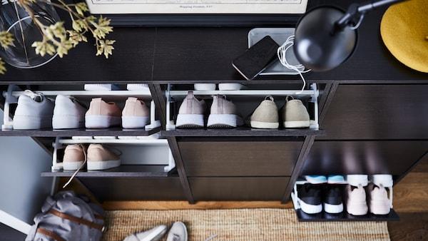 Eteisessä on kolme tummanruskeaa BISSA- kenkäkaappia, joiden auki olevissa lokeroissa on kenkäpareja rivissä.
