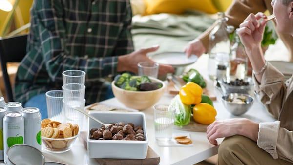 Etenstijd met jonge mensen rond een tafel waarop verschillende soorten voeding staan, waaronder plantaardige balletjes.