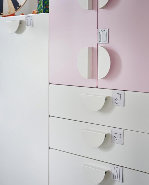 Etikettenhalter mit Abbildungen von Kleidungsstücken sind an den Schubladen und Türen eines Kleiderschranks in Weiß/Blassrosa angebracht.