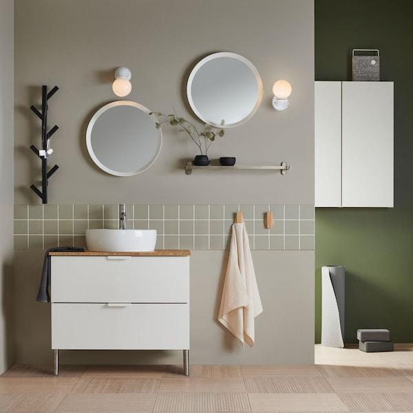 Ett badrum med kommod och speglar