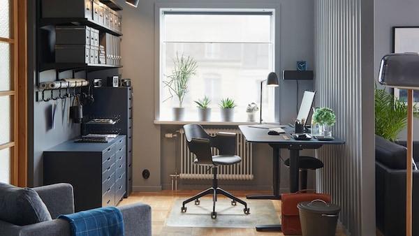 Ett blått/svart BEKANT sitt-/ståskrivbord i linoleum i ett färgkoordinerat hemmakontor med en konferensstol och förvaring.
