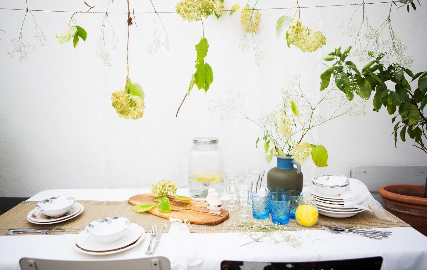 Ett bord dukat med mönstrat porslin, glas och en vas med blommor. Över bordet hänger blommor.