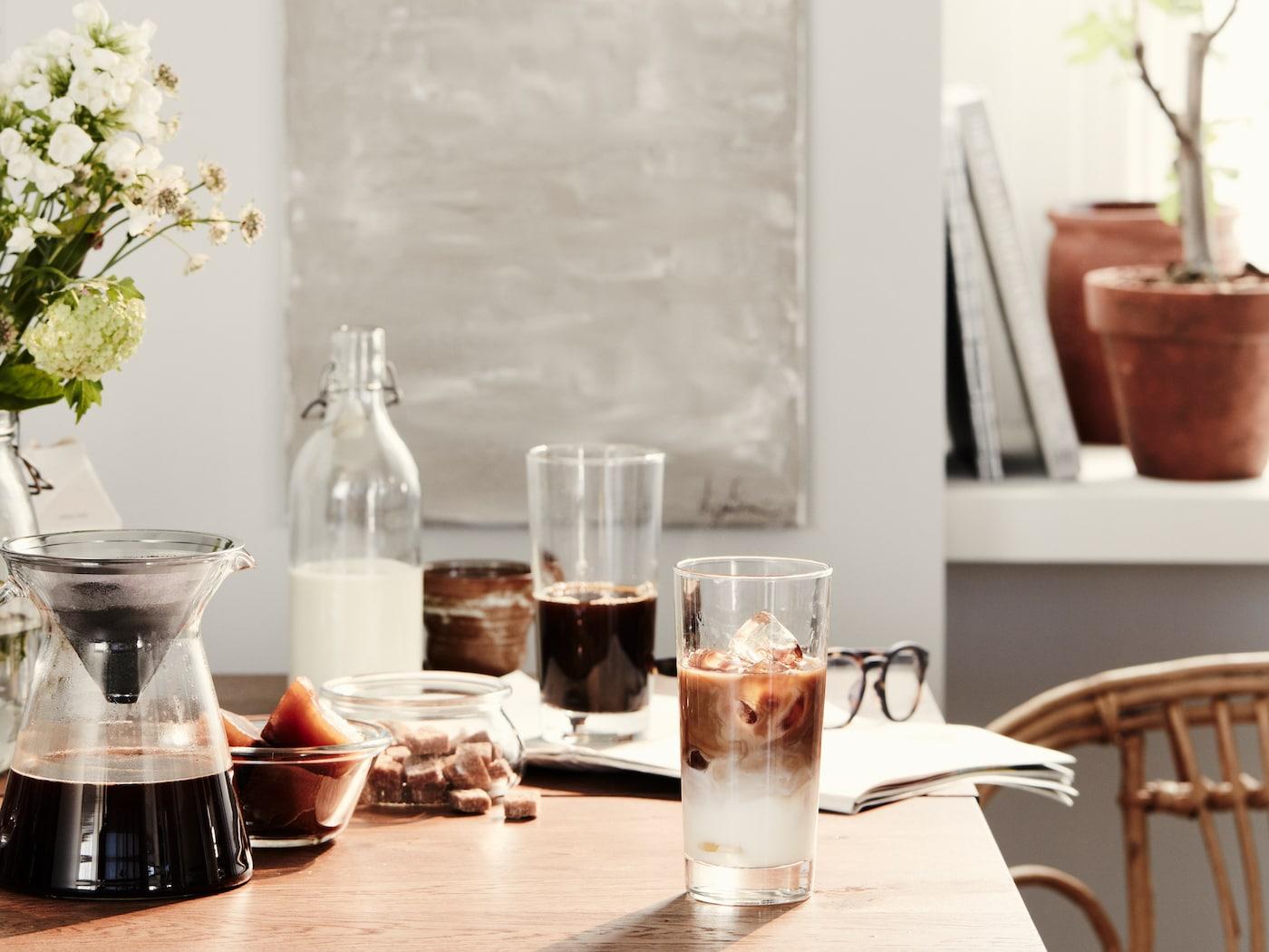 Ett bord med långfrukost uppdukat. På bordet i trä står höga glas med iskaffe i.