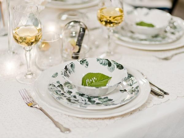 Ett dukat kuvert med vit tallrik, assiett och skål i en lantlig och rustik design med en mjuk volangkant med vackra gröna löv.