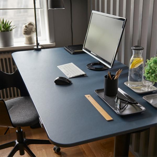 Ett ergonomiskt blått/svart BEKANT sitt-/ståskrivbord i linoleum med en datorskärm, en vattenflaska, ett glas och diverse andra kontorssaker.
