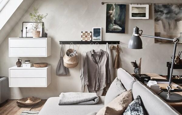 Ett extrarum med sluttande tak har möblerats med möbler i neutrala färger, bland annat en bäddsoffa och ett skrivbord.
