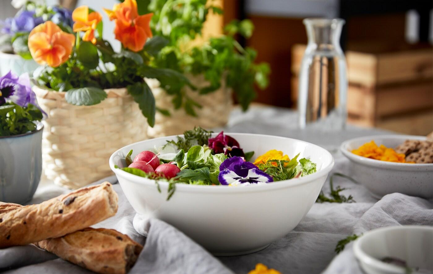 Ett frukostbord dukat med olika typer av bröd, blomkrukor och en skål med färgglatt garnerade grönsaker.