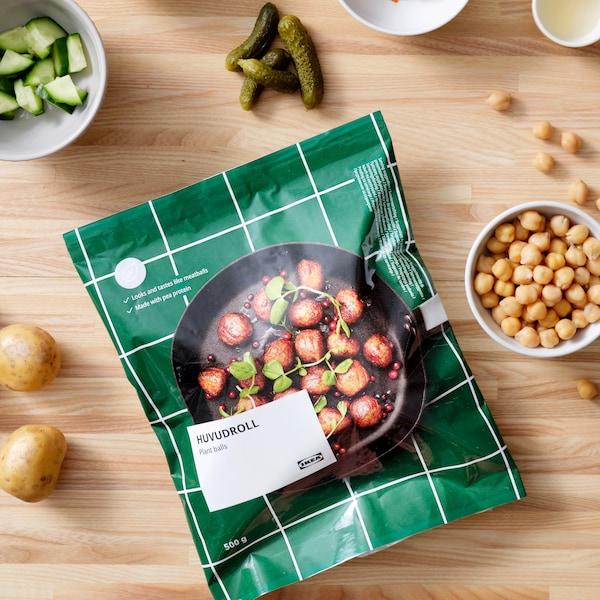 Ett grönt paket med plantbullar från IKEA ligger på en  bänkskiva i ljust trä