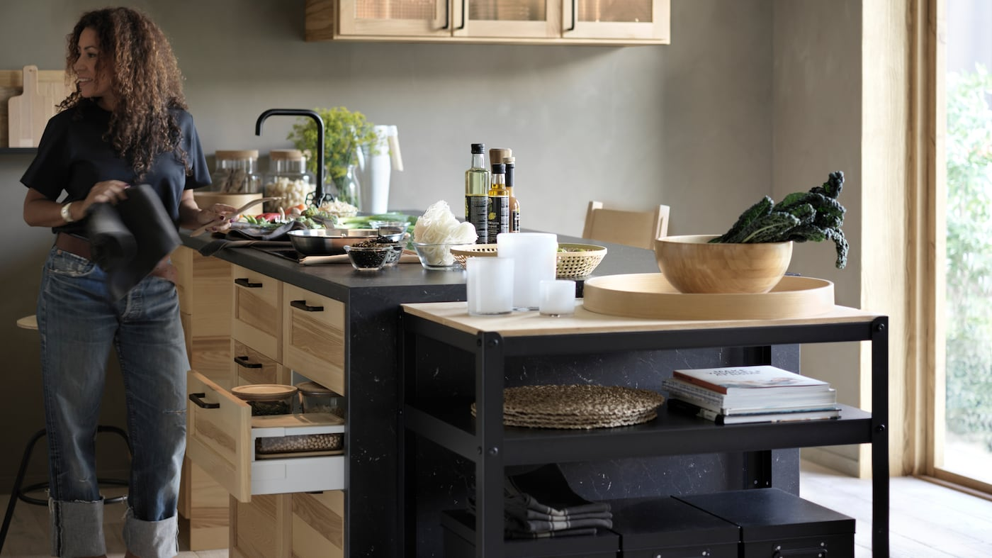 Ett kök i svart och natur där en kvinna förbereder veckans matlådor.