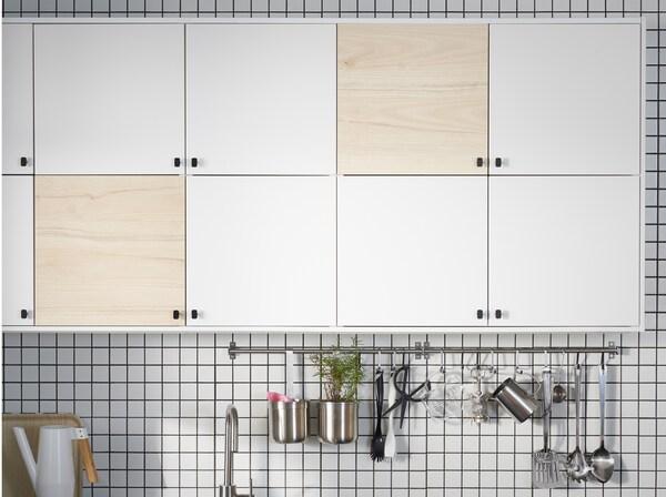 Ett kök med dörrar i vitt och ljust askmönster, två stänger i rostfritt stål och en vit vattenkanna.
