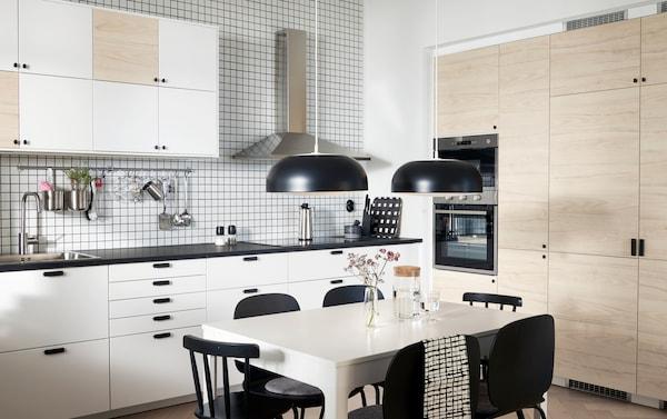 Ett kök med dörrar i vitt och ljust askmönster, två svarta taklampor, ett vitt bord och svarta stolar.