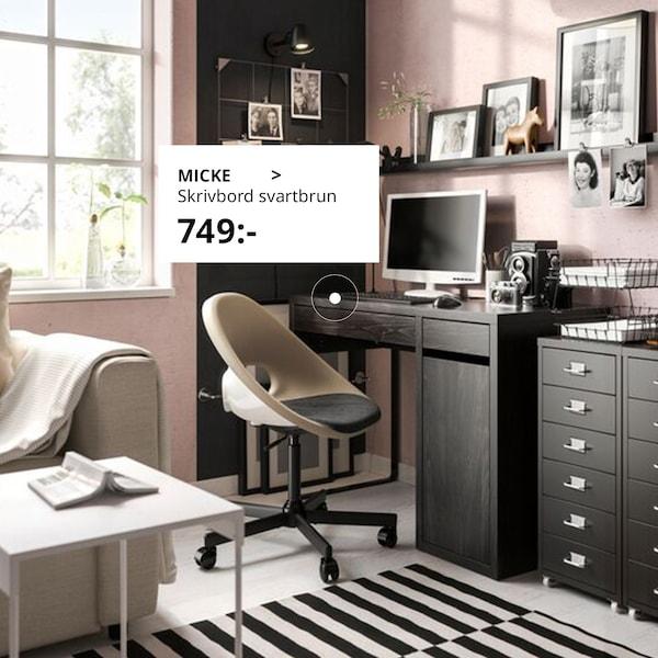 ett ljusrosa hemmakontor med möbruna kontorsmöbler och en beige kontorsstol. På golvet ligger en stor svartvitrandig ullmatta