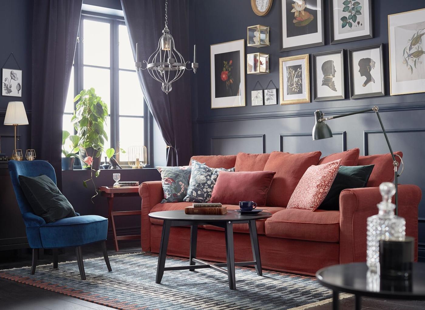 ett mörkmålat vardagsrum där en röd soffa står mot en vägg där ett härligt tavelkollage med olika ramar sitter uppsatt.