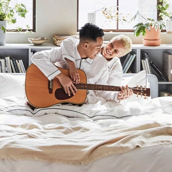 Ett par i ett ljust sovrum som sitter i en bekväm, mysig säng med mjuka textilier och spelar gitarr.