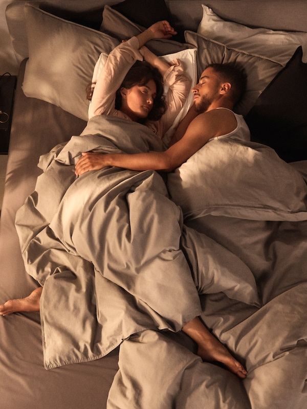 Ett par sover tätt tillsammans i en säng, kvinnan har armarna ovanför sitt huvud och mannen har ena sin arm över kvinnans mage