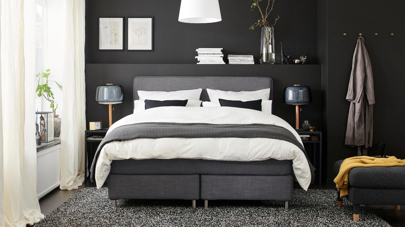 Ett Sovrum i grått med en säng i grått som står mitt i rummet i rummet bäddade med sängkläder i vitt, grått och svart.