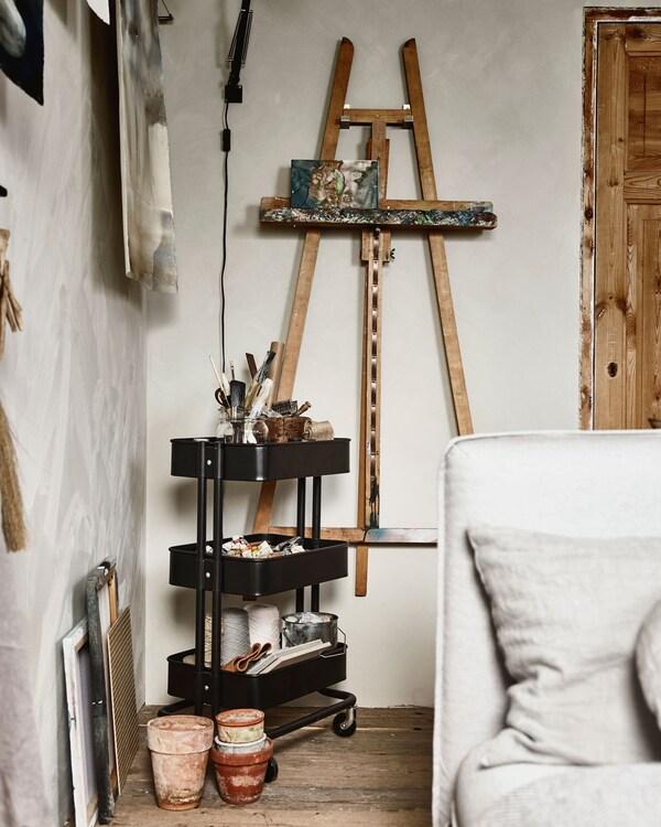 Ett stativ hänger på väggen, och bredvid står en rullvagn med konstmaterial.