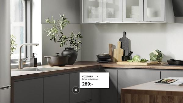 Ett stilrent kök i grått med accessoarer i svart och trä samt vitrinskåp på en vägg.