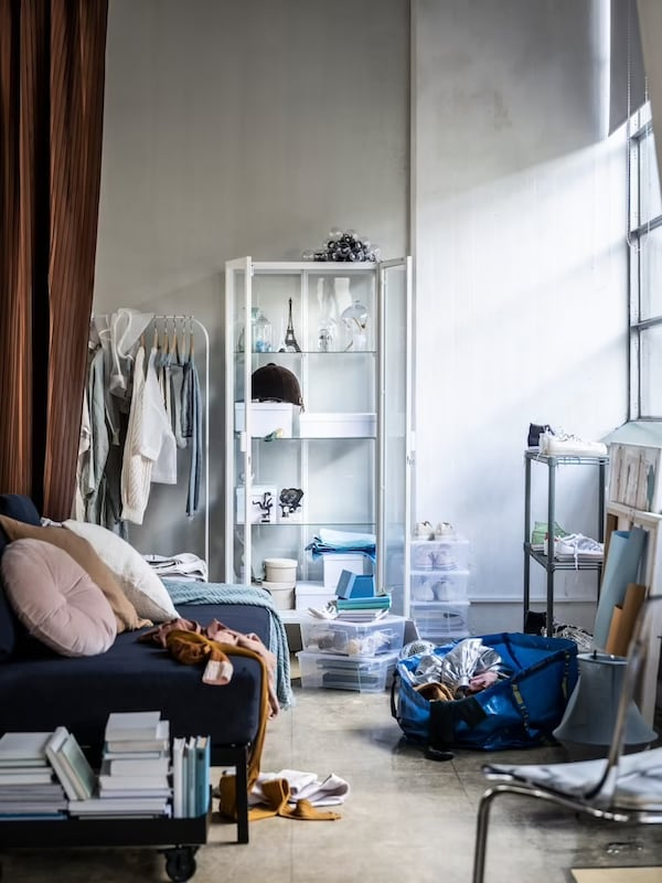 Ett stökigt rum med plädar, kläder och genomskinlig lådor som står framme