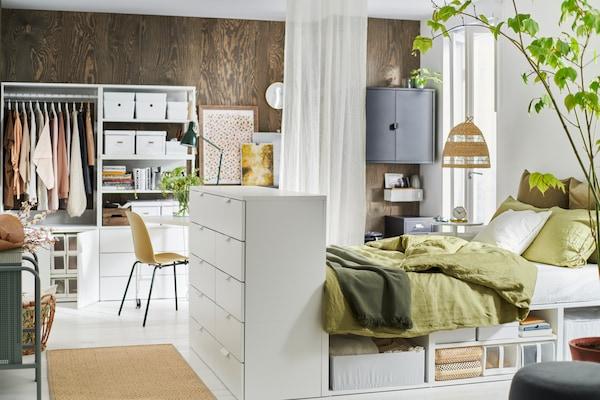 Ett stort ljust sovrum med PLATSA säng med förvaring och garderober.