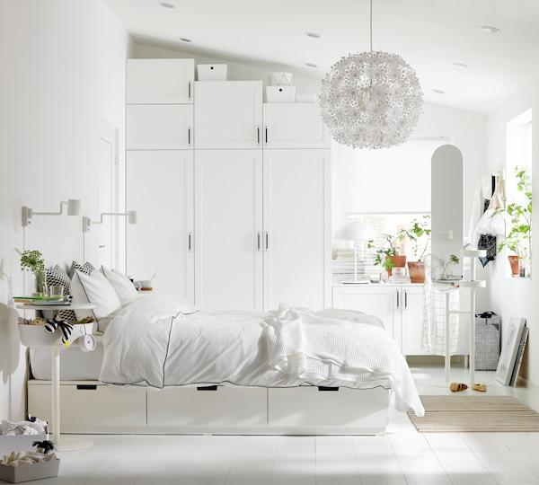 Ett stort ljust sovrum med vita säng och garderober som passar en snedtak.