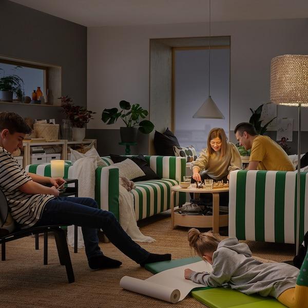 Ett vardagsrum centrerat kring två grön- och vitrandiga soffor, där en familj ritar och spelar schack.
