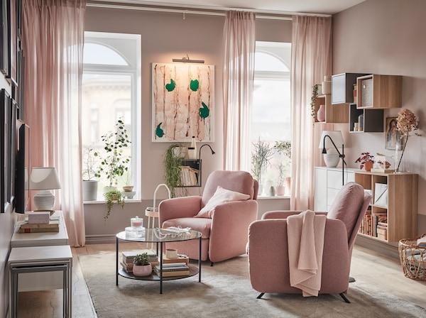 Ett vardagsrum med två EKOLSUND vilfåtöljer med ljust brunrosa GUNNARED klädsel som står framför fönster som släpper in dagsljus.