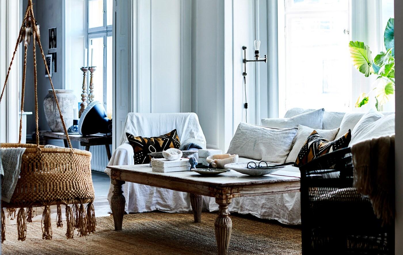 Ett vardagsrum med vit soffa, rustikt bord och hängande rottingvagga.