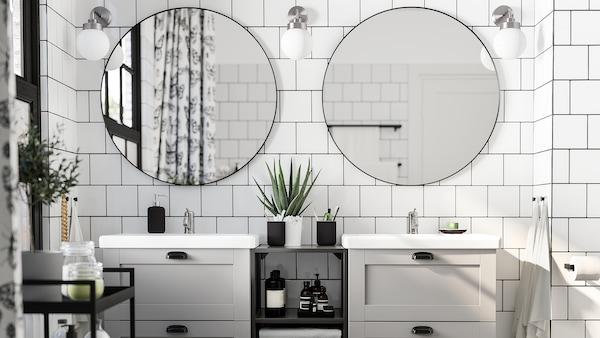 Ett vitkaklat badrum med två runda speglar, två tvättställ i grått och vitt, en svart vagn och tre vägglampor.