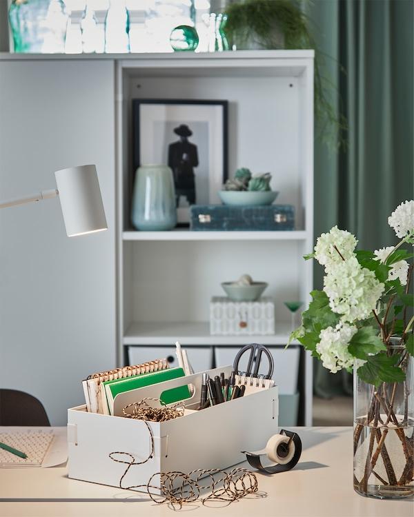Ett vitt förvaringstillbehör är placerat på ett vitt skrivbord i ett sovrum. I förvaringstillbehöret förvaras pennor, anteckningsblock och annat.